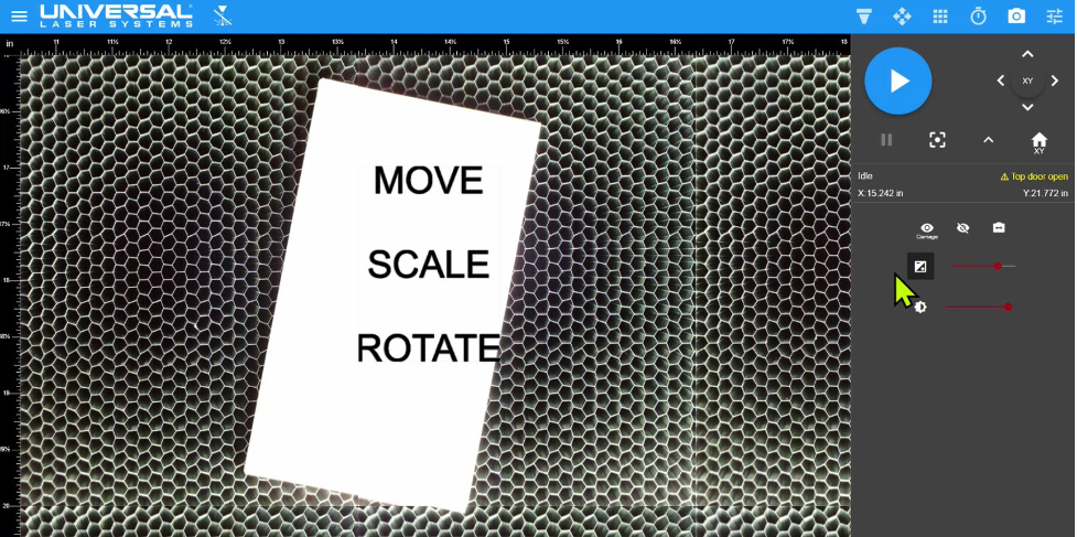<i>Close-up view in the Laser System Manager (LSM) of the material placed on the Multifunction Material Support Structure provided by the carriage camera. In this example the design file consisting of text (MOVE, SCALE, and ROTATE) is positioned over the material. The design file can be any laser compatible graphic.</i>